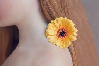 Frau mit Blume auf der Schulter